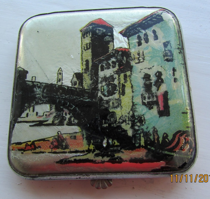 Small square compact with polished metal mirror and sifter in place. The picture is showing tall buildings and a bridge. The coral coloured back has small sratches but the front is perfect. A very pretty compact.