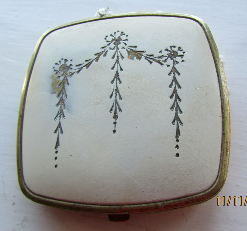 This small cream-coloured compact is of good quality. There is a polished metal mirror that lifts to reveal a rouge well and a powder well. The back of the compact is cream and there is lovely scrolling to the edges.