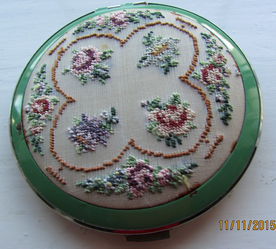 Compact with green surround and embroidered centrepiece