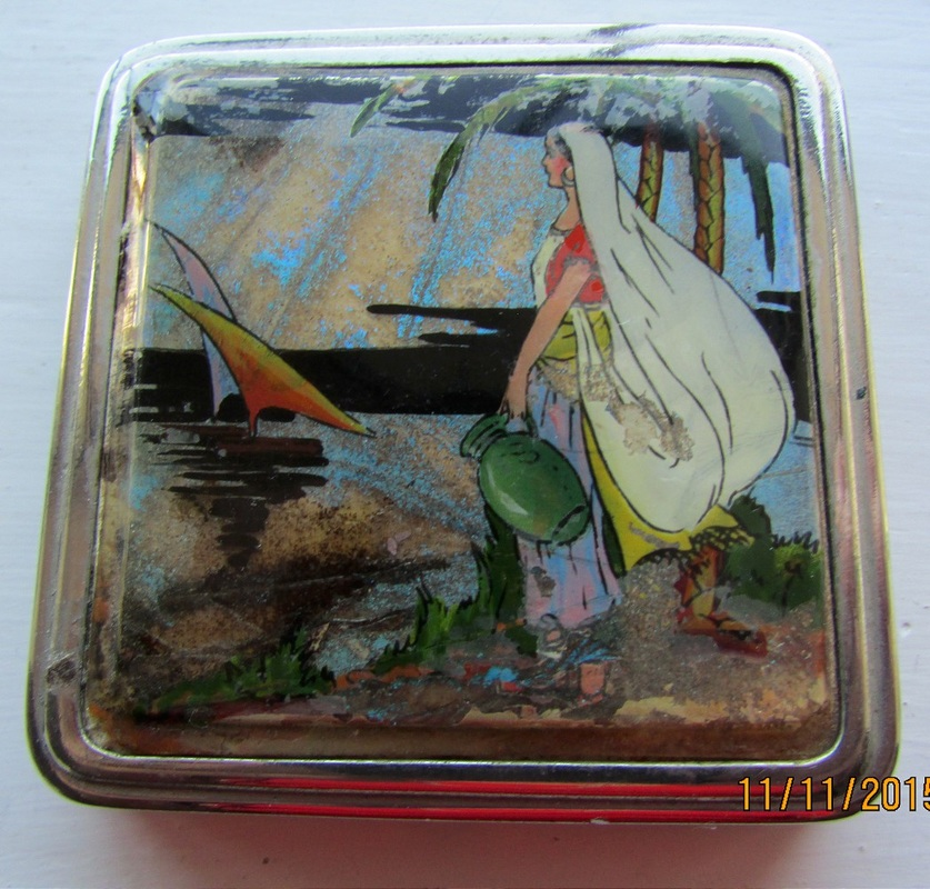 A small square compact with polished metal mirror and powder wheel. The picture is girl in flowing veil carrying a jug and there are sails in the distance