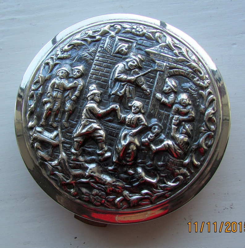 Silver coloured compact with fiddler and dancers